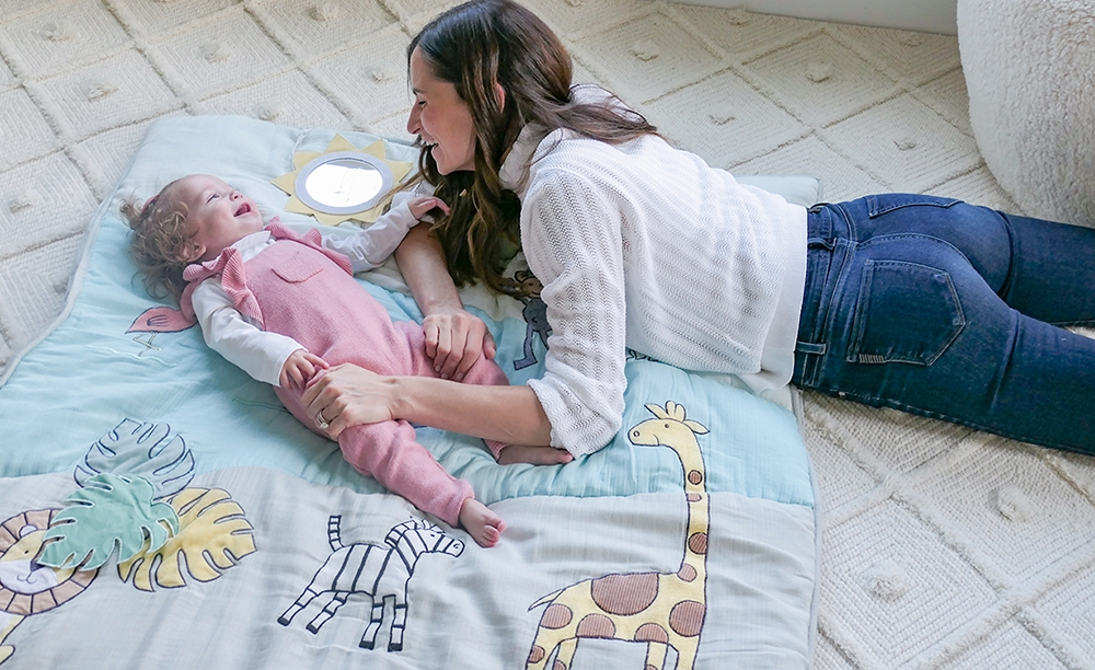 mom and daughter playing on aden + anais baby bonding playmat