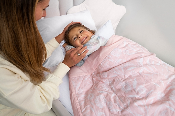 mom tucking toddler girl into bed with toddler-bed weighted blanket