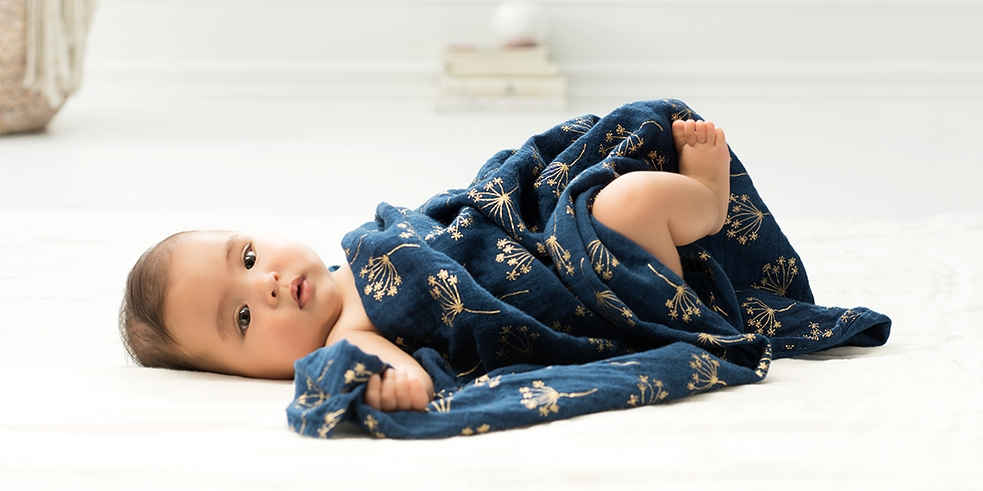 aden + anais baby with a muslin swaddle