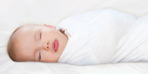 Cute sleeping baby swaddled in Aden and Anais blanket