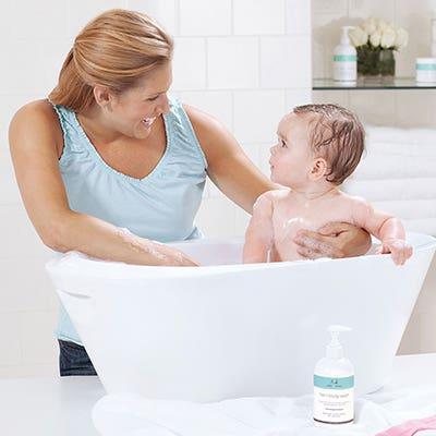 Mom bathes baby - Aden and Anais